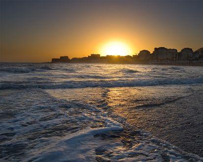 Обои Солнце встаёт над городом, на переднем плане неспокойное море