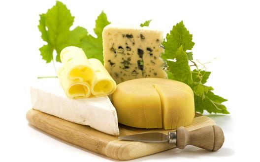 Обои Швейцарские сыры на деревянной доске украшенные листьями винограда и сырный нож