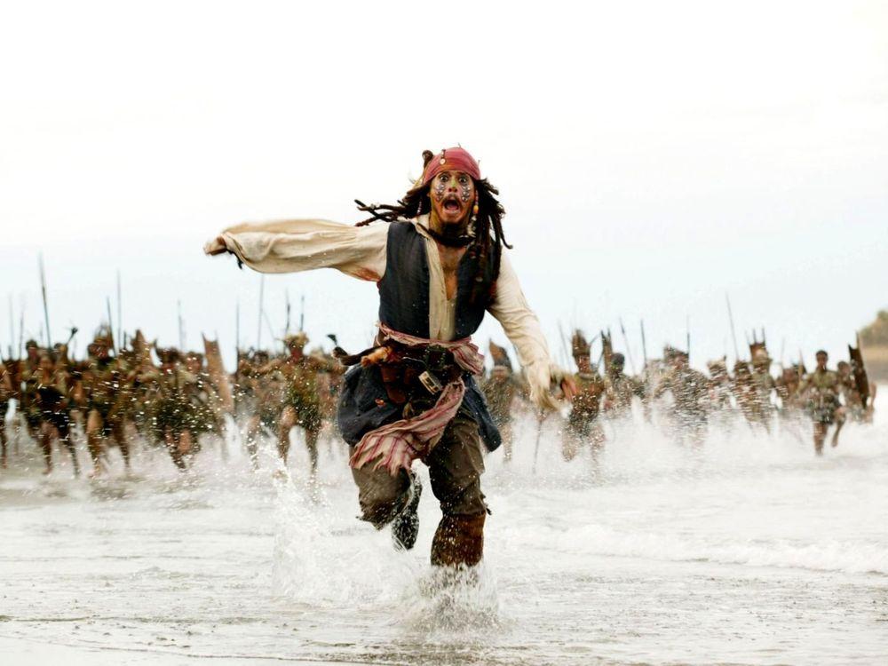 Обои для рабочего стола Капитан Джек Воробей убегает от разгневанных туземцев (Пираты Карибского моря Сундук мертвеца - 2)