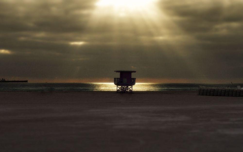 Обои для рабочего стола Сквозь плотную пелену облаков прорываются тусклые лучи солнца и освещают берег моря и чаек
