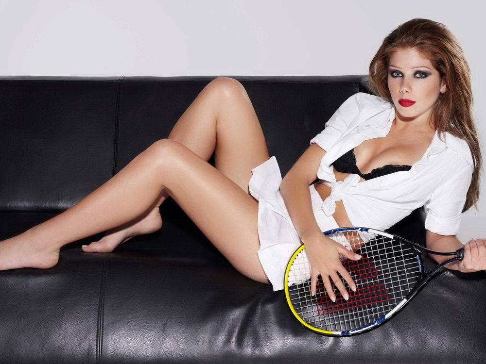 Обои для рабочего стола Девушка лежит на диване с теннисной ракеткой
