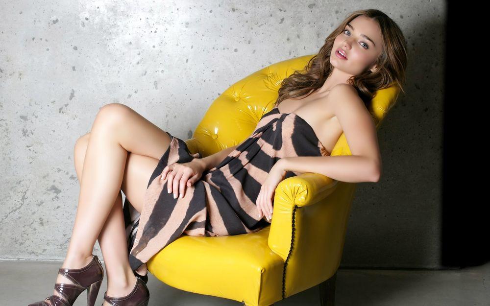 Обои для рабочего стола Модель Victoria`s Secret Миранда Керр / Miranda May Kerr сидит на жёлтом кресле