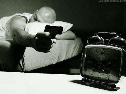 Обои Мужчина направил на будильник пистолет, явно не желая просыпаться