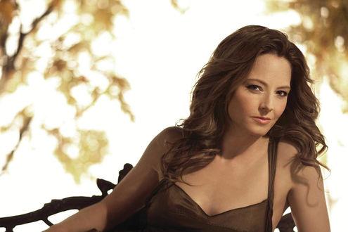 Обои Джоди Фостер в коричневом платье лежит в осеннем лесу