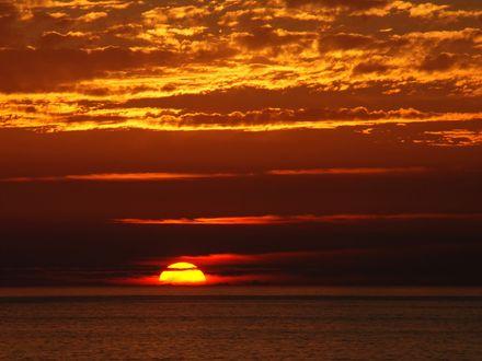 Обои Золотое солнце скрывается за морем