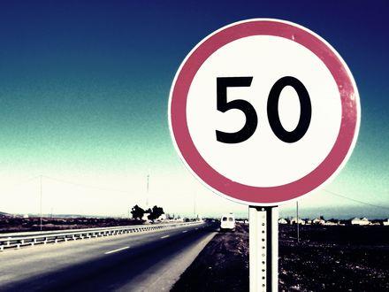 Обои На обочине дороги стоит знак ограничения скорости 50 км/ч