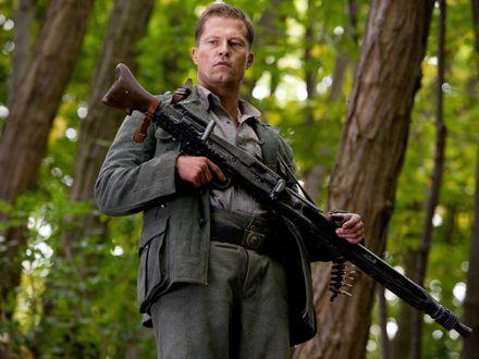 Обои Немецкий актер Тиль Швайгер / Til Schweiger с винтовкой в лесу
