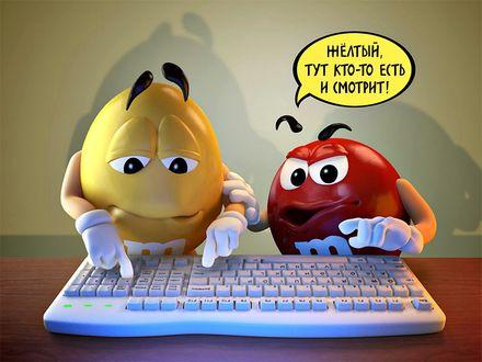 Обои Желтый m&m's набирает что-то на компьютерной клавиатуре в то время как Красный указывая пальцем говорит ему (Желтый, тут кто-то есть и смотрит!)