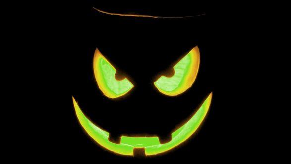 Обои Жутко улыбающийся «светильник Джек» с зелёным свечением в отверстиях глаз и рта на чёрном фоне