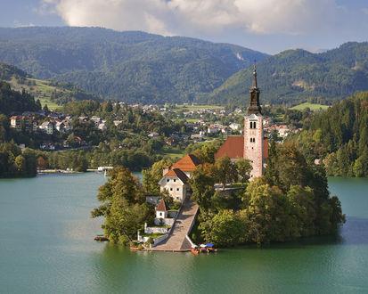 Обои Маленький остров с церковью посередине озера на фоне не большого города в горах Slovenija / Словении