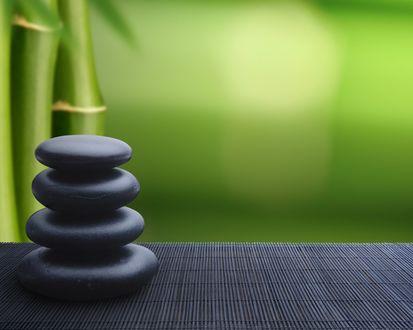 Обои Пирамида из четырёх чёрных камней на столе на фоне зелёного бамбука