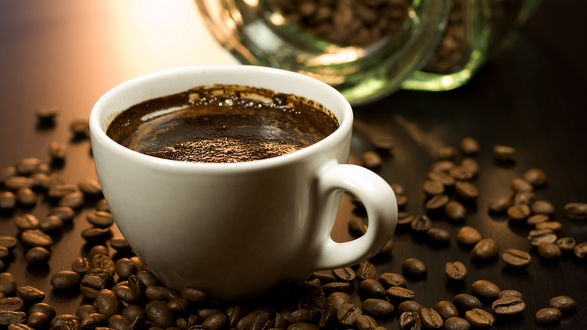 Обои Чашка кофе стоит на зёрнах