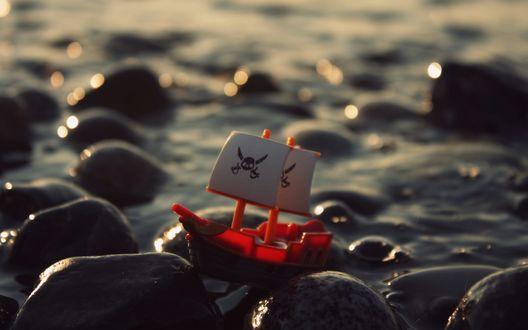 Обои Игрушечный пиратский кораблик на камнях