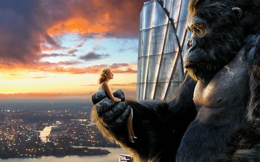 Обои Кинг-Конг держит в лапе обворожительную блондинку, на фоне этой картины раскинулся огромный город