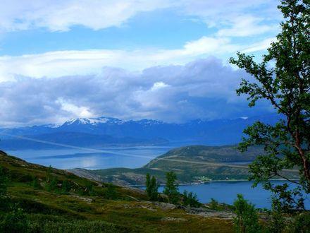 Обои Изрезанные морем холмистые берега, вдали снежные шапки гор