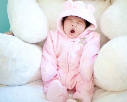 Обои Зевающий малыш в розовом комбинезончике возле мягкой игрушки