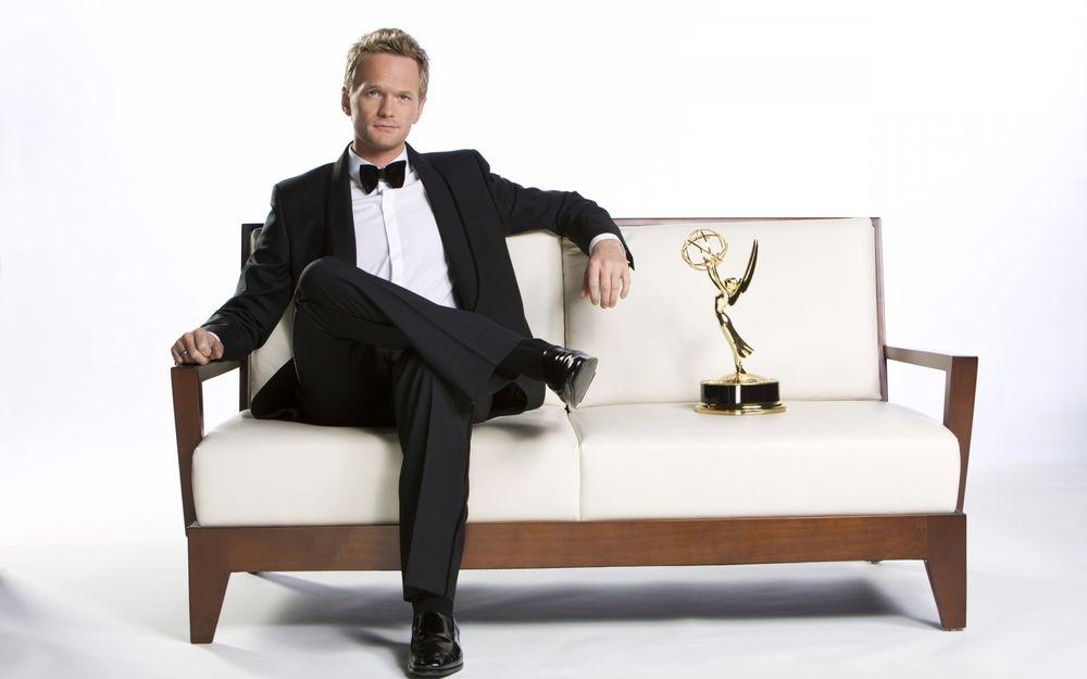 Обои для рабочего стола Актер Нил Патрик Харрис / Neil Patrick Harris в костюме с бабочкой сидит на белом диване возле награды
