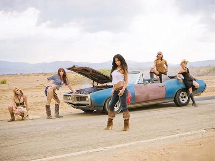 Обои Пять девушек из группы Pussycat Dolls стоят на дороге около старой сломанной машины