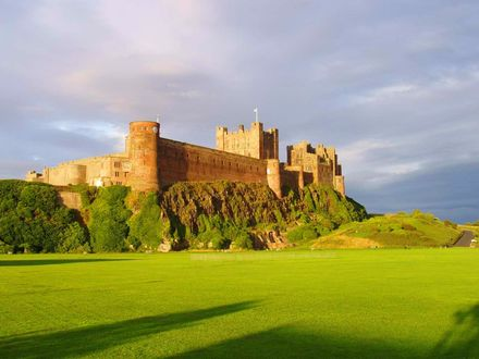 Обои Замок Бамбург /  Bamburgh Castle на горе, окруженный зеленым лугом, графство Нортумберленд / Northumberland, Великобритания