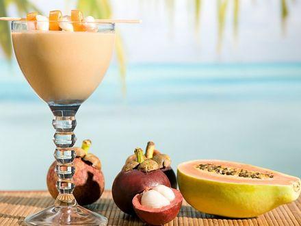 Обои Коктейль с тропическими фруктами на столе у моря