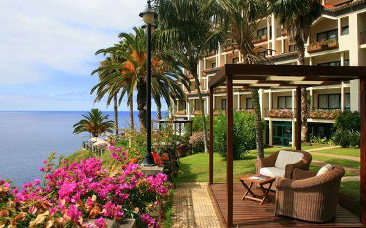 Обои Беседка с плетеной мебелью с видом на море среди пальм на тропическом курорте