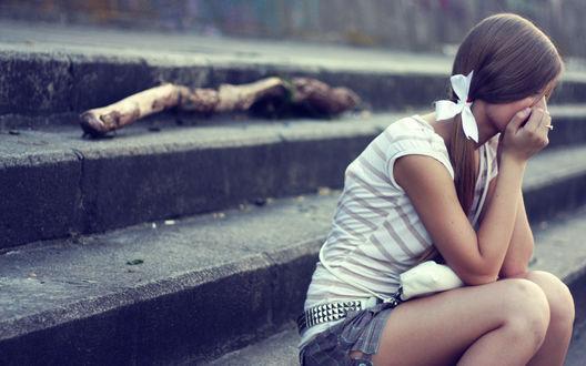 Обои Девушка сидит на ступеньках закрыв лицо руками и плачет