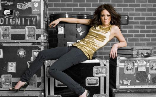 Обои Актриса Хилари Дафф / Hilary Duff сидит на чемоданах в золотом топе, джинсах и туфлях