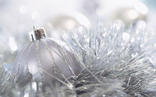 Обои Новогодний шар среди серебряного дождика