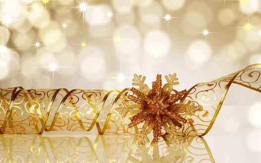 Обои Новогоднее украшение золотая снежинка и золотая ленточка рядом