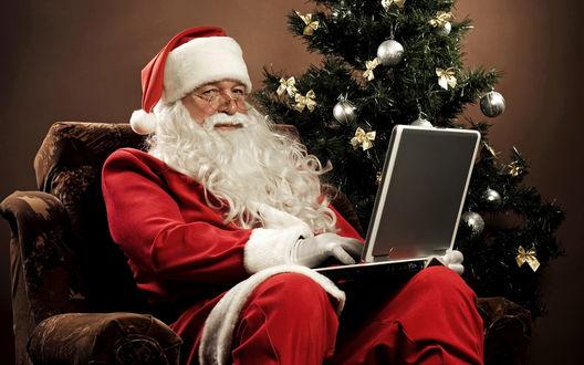 Обои Санта Клаус сидит за ноутбуком