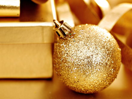 Обои Золотой новогодний шар возле коробок с подарками