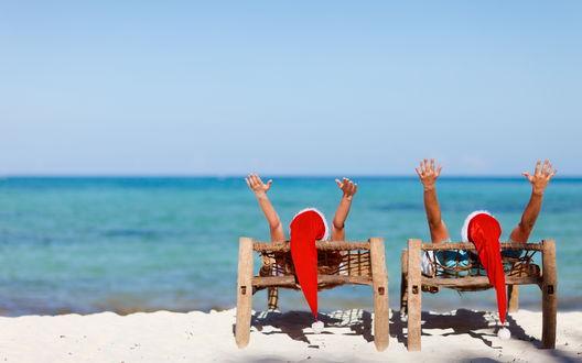 Обои Пара прзднует новый год в шапках Санты на берегу моря