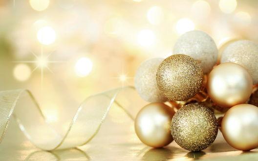 Обои Золотые новогодние шары, сложенные кучкой и золотая лента