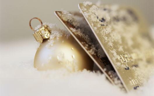 Обои Новогодний шар и золотые кредитные карты в снегу