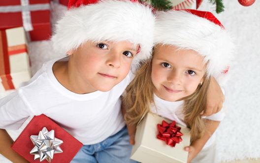 Обои Мальчик и девочка в новогодних шапках с подарками в руках