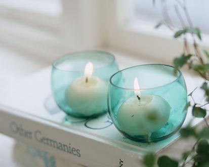 Обои Свечи в голубых подсвечниках стоят на окне на стопке книг, рядом вьющееся растение, и все это создает  атмосферу теплого домашнего вечера (Other Germans)