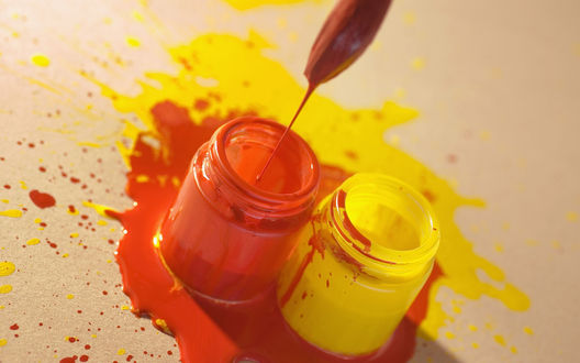Обои На столе стоят две краски -  желтая и красная гуашь
