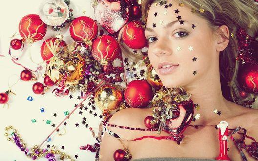 Обои Девушка, с звёздочками на лице, лежит в красных , елочных игрушках