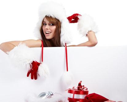 Обои Симпатичная девушка в новогоднем наряде выглядывает из большого подарочного пакета, рядом лежат подарки