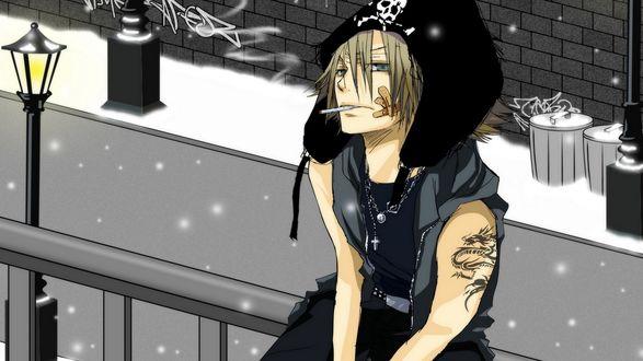 Обои Гокудера Хаято из аниме Репетитор-киллер Реборн в чёрной шапке-ушанке с черепом, с татуировкой дракона на плече и сигаретой во рту зимой на улице сидит возле фонаря