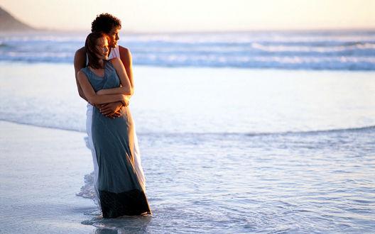 Обои Влюбленная пара на берегу, парень обнял девушку, и они вместе смотрят на спокойные морские волны