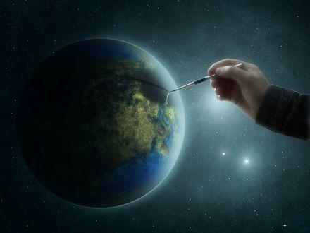 Обои Рука с кисточкой разрисовывает планету Земля