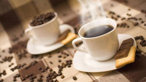 Обои Две чашки кофе стоят на столе с кусочками шоколадом