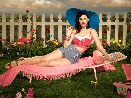 Обои Певица Кэти Перри / Katy Perry, одетая в ретро стиле (пинап) прилегла в саду на шезлонг