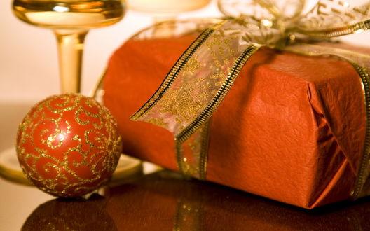 Обои Подарок с лентой и новогодняя игрушка на столе с бокалом