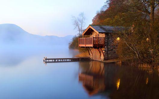 Обои Осень. В рассветной дымке тумана еле видны очертания гор, а вплотную к озеру подступает каменный дом с причалом для лодок