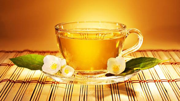 Обои Кружка чая стоит на блюдце в котором лежат белые цветки жасмина