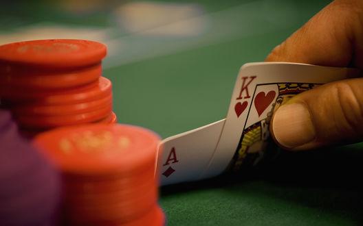 Обои Игрок смотрит на карты при игре в покер, король, туз и красные фишки на зеленом сукне