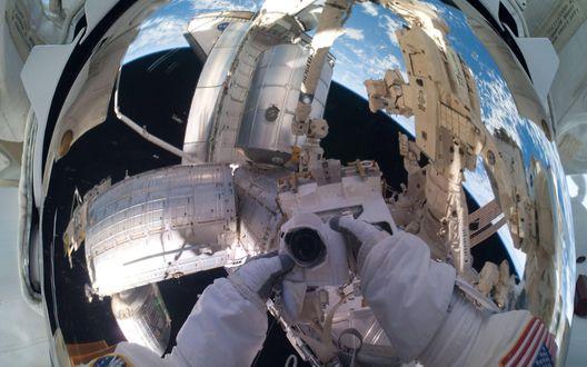 Обои Космонавт сфотографировал своё отражение в скафандре