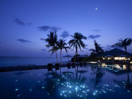 Обои Романтический тихий вечер на тропическом курорте, бассейн подсвечен десятками подводных огоньков, волны бесшумно ласкают берег, нигде ни души - все собрались в бунгало на ужин